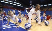 Kansas ensure Travis Releford gets down for chase dog pushups subsequent to 8-year-old Tyler Peterson, left, Topeka, on Tuesday, Dec. 27, 2011, during a Holiday Hoops Clinic during Allen Fieldhouse. The pushups, that were systematic by executive of basketball operations, Barry Hinson, consisted of lifting one's conduct adult and utterance like a dog.